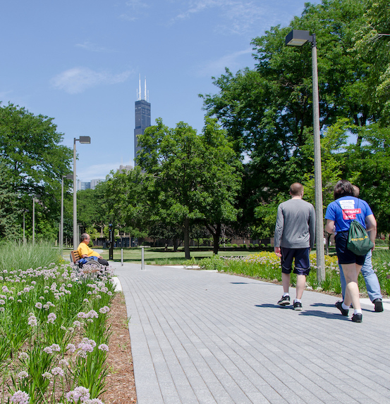 students walking toward the Sears (Willis) Tower on a campus path