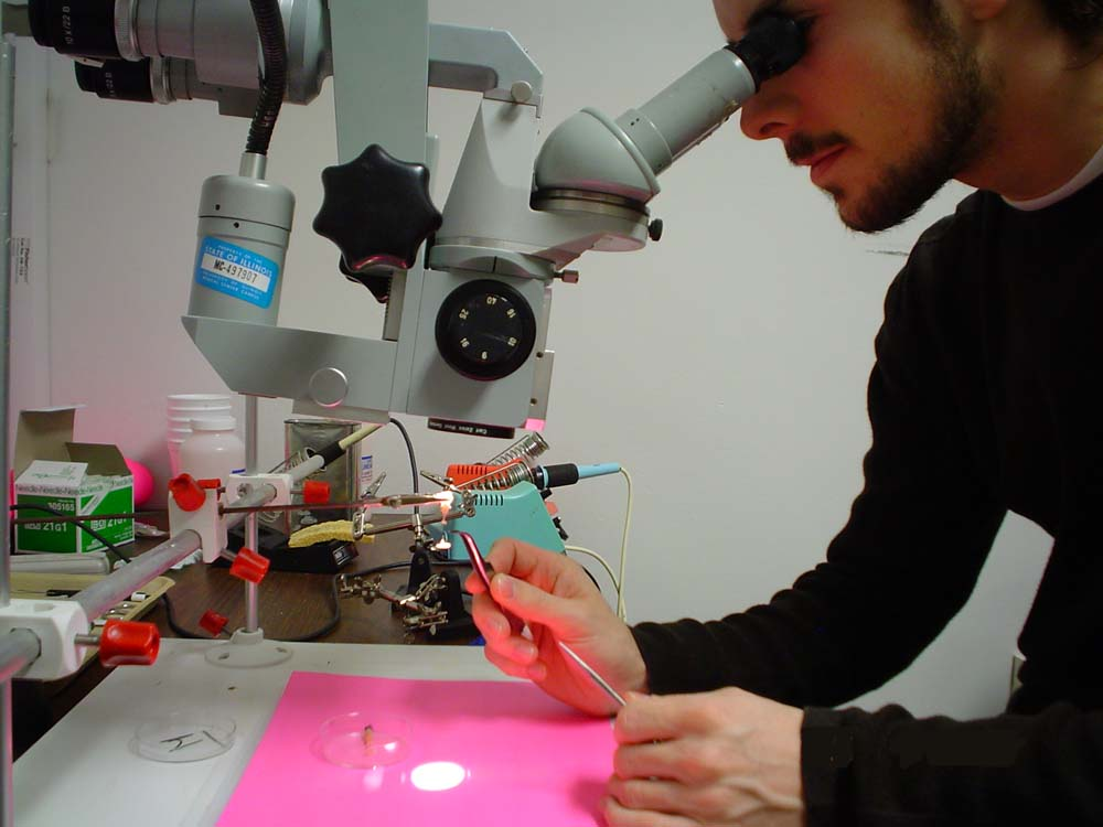 student examining something under microscope