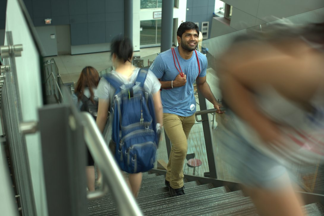 UIC graduate student ascending a staircase