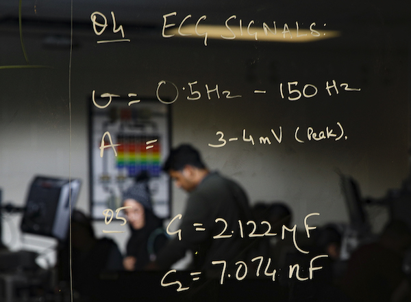 two students working in the Bioinstrumentation Lab, with a clear-screen blackboard in the foreground